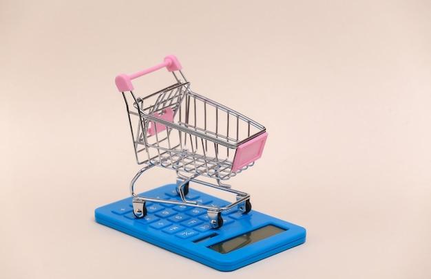 Custo de mercado. mini carrinho de compras com calculadora em fundo bege