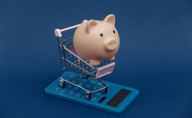 Custo de mercado. mini carrinho de compras com cofrinho e calculadora no fundo azul clássico