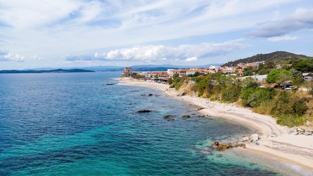 Custo do mar egeu da grécia, ouranoupolis, edifícios e torre de prosphorion, costa rochosa, vista do drone, grécia