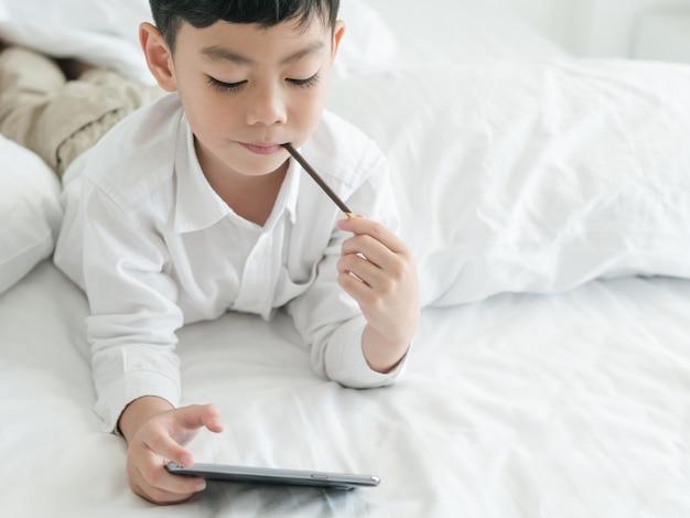 Cute, asian asian, criança, focalizado, em, smartphone, enquanto, encontrar-se cama