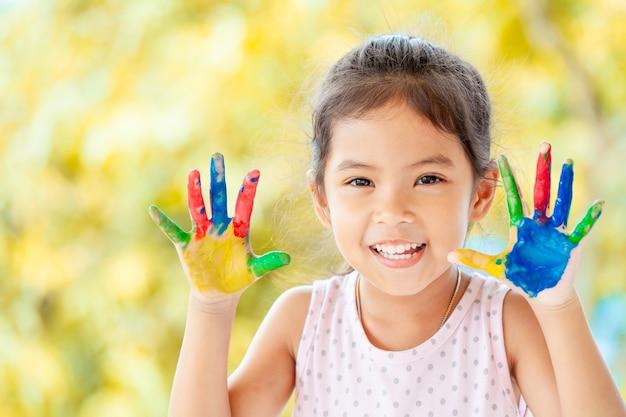 Cute, asian menina criança, com, pintado, mãos, sorrindo, com, divertimento, e, felicidade