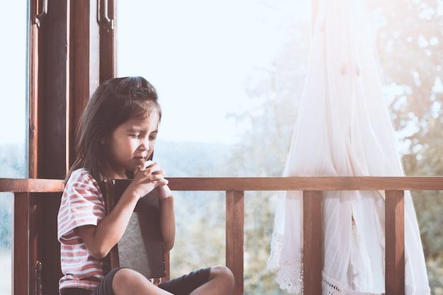 Cute, asian menina criança, orando, com, dobrado, dela, mão, em, a, sala