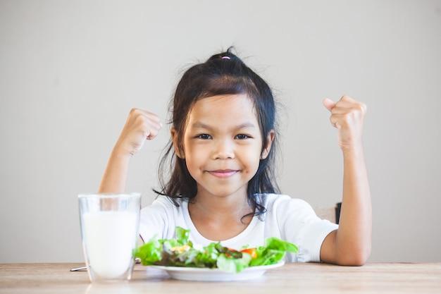 Cute, criança asiática, menina, comer, legumes saudáveis, e, leite, para, dela, refeição