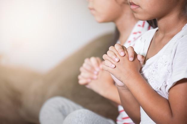 Cute, criança asiática, menina, e, dela, irmã, orando, com, dobrado, dela, mão, em, a, sala, junto