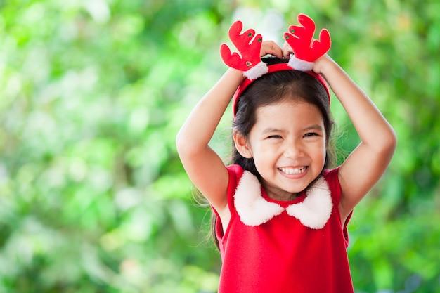 Cute, criança asiática, menina, em, vestido natal, sorrindo