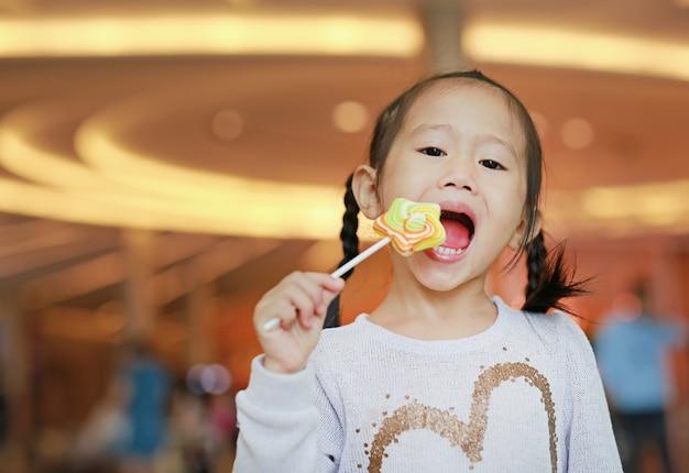 Cute, criança pequena, menina, comer, estrela pirulito, doce