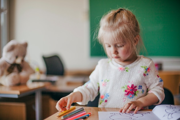 Cute girl sitting and drawing