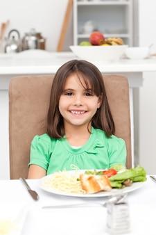 Cute little girl comendo macarrão e salada