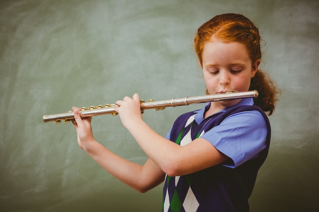 Cute little girl playing flute in classroom