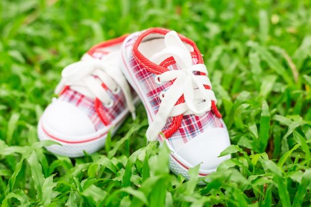 Cute little sapatinhos de bebê vermelho e branco na grama verde