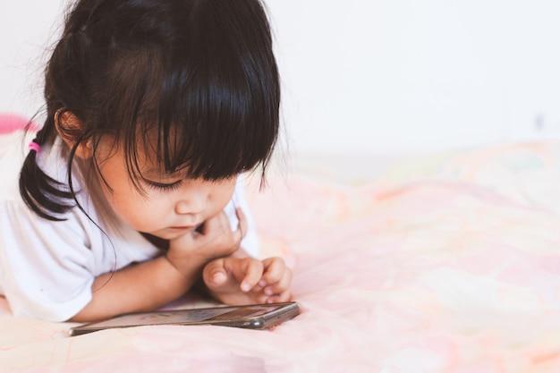 Cute, menina bebê asiático, tocando, smartphone, mentindo, ligado, dela, cama, em, dela, sala