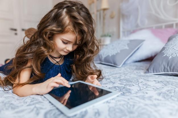 Cute, menininha, com, cabelo ondulado, usando, tablete digital