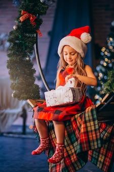 Cute, menininha, em, chapéu santa, desembalando, presente natal