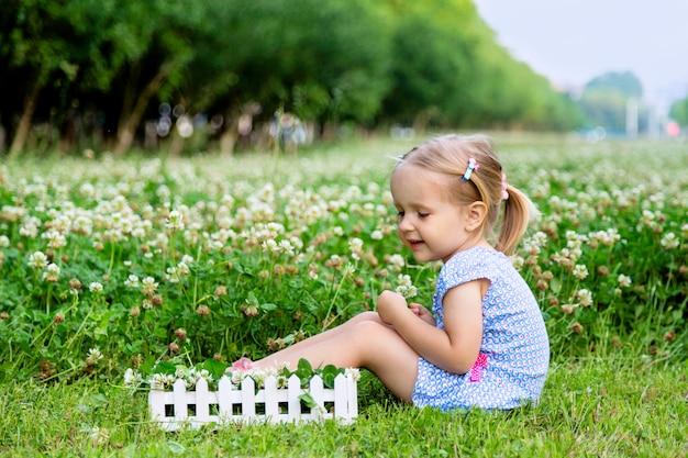 Cute, menininha, sentando, ligado, um, trevo, campo