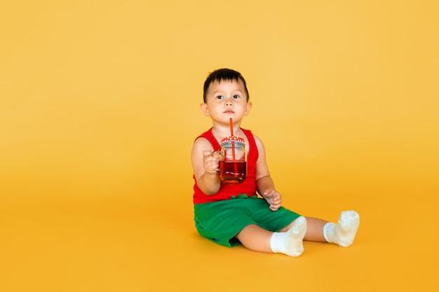 Cute, menino bebê, em, vermelho, t-shirt, e, verde, shortinho, com, copo suco, ligado, amarela
