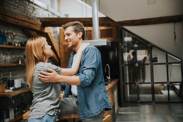 Cute, par jovem, abraçando, enquanto, cozinhar, em, seu, cozinha