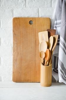 Cutelaria de madeira ou de bambu, toalha e placa de corte no interior da cozinha branca.