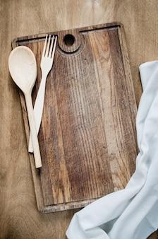Cutelaria rústica com a toalha de cozinha na placa de madeira.