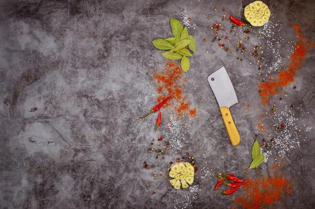 Cutelo de utensílios de cozinha e especiarias em fundo escuro.