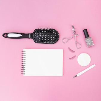 Cutícula; escova de cabelo; esponja; pestanas falsas; curvex de cílios; garrafa de esmalte com bloco de notas em branco espiral no pano de fundo rosa