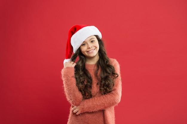 Cutie brincalhão. adorável garota com cabelo longo encaracolado usa fundo de chapéu vermelho de papai noel. contando dias até o natal. festa de natal para crianças e alunos. conceito de convite de férias de natal.