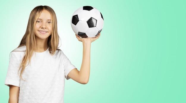 Cutie menina na camisa branca, segurando uma bola de futebol nas mãos