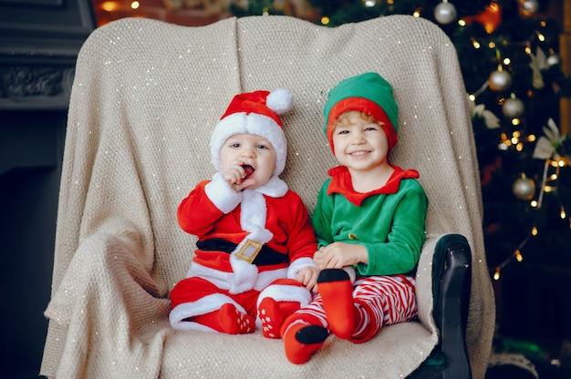 Cutte irmãozinhos em casa perto de decorações de natal