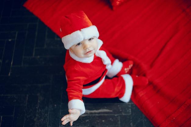 Cutte menino em casa perto de decorações de natal