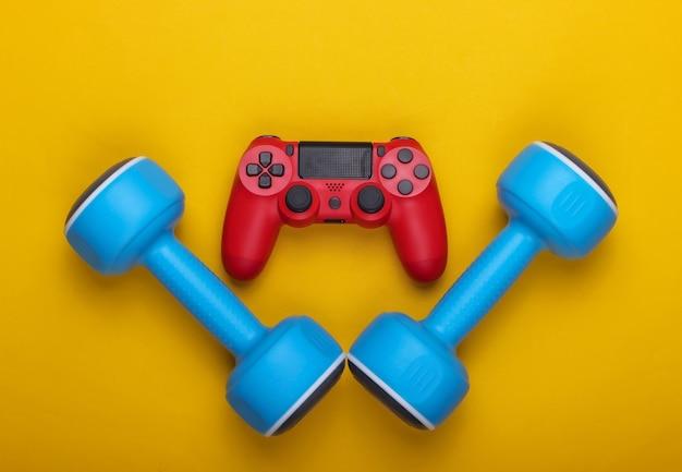 Cybersport. esporte e entretenimento. gamepad e halteres em um amarelo