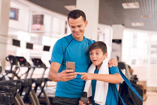 D está de pé com telefone no ginásio e seu filho faz amizade com ele.