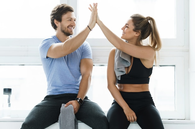 Dá cá mais cinco entre homem e mulher no ginásio após o treino de fitness. personal trainer e seu cliente alcançando resultados durante um treinamento.