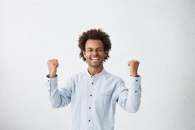 Da cintura para cima, foto de estúdio de um estudante mestiço bem-sucedido com um corte de cabelo afro exclamando