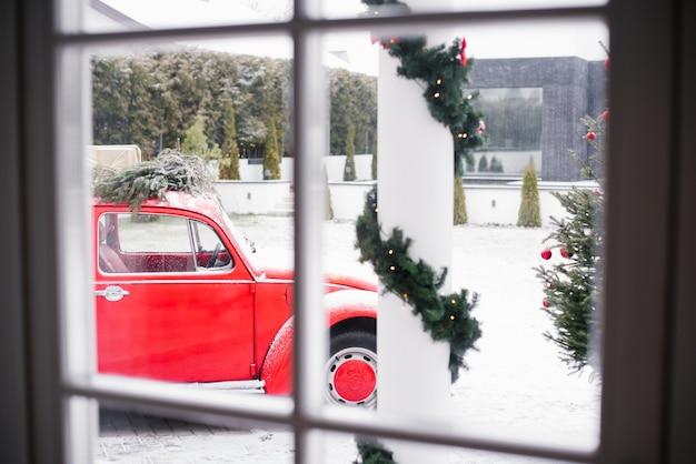Da janela da casa você pode ver um carro vermelho com uma árvore de natal no telhado dia de inverno