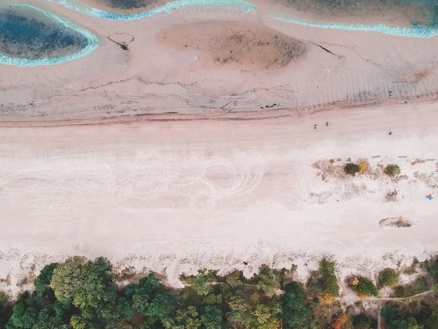 Da praia do mar báltico. ondas azuis, cristas de areia, pegadas na areia.