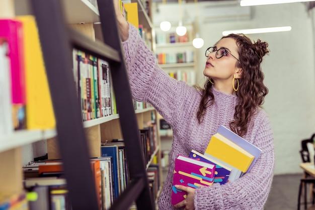 Da prateleira mais alta. jovem curiosa com um suéter de tricô roxo esticando a mão enquanto lê o livro gostei
