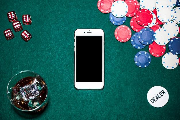 Dadinhos vermelhos; copo de uísque; fichas de casino; chip de revendedor e celular na mesa de poker