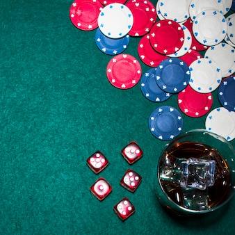 Dadinhos vermelhos; fichas de casino e copo de uísque na mesa de poker verde