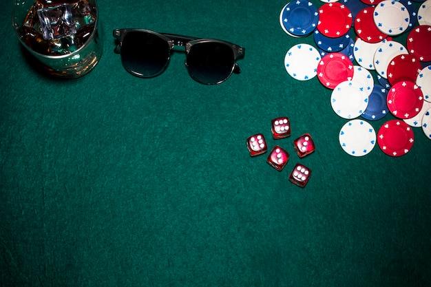 Dadinhos vermelhos; fichas de casino; óculos de uísque e óculos de sol em fundo verde poker