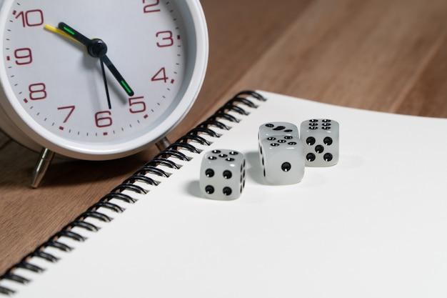 Dados colocados no caderno vazio com o despertador branco do vintage na tabela de madeira.