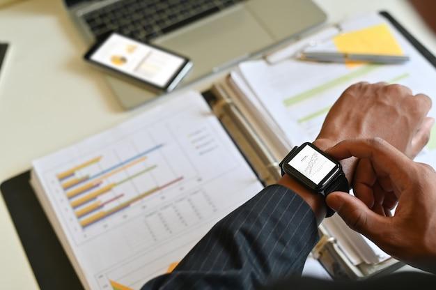Dados da análise do homem de negócios no relógio esperto na mesa de escritório.