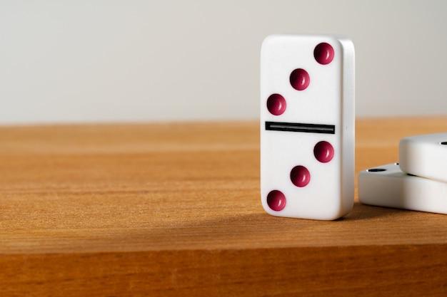 Dados de dominó branco em pé na mesa de madeira fechar Foto Premium