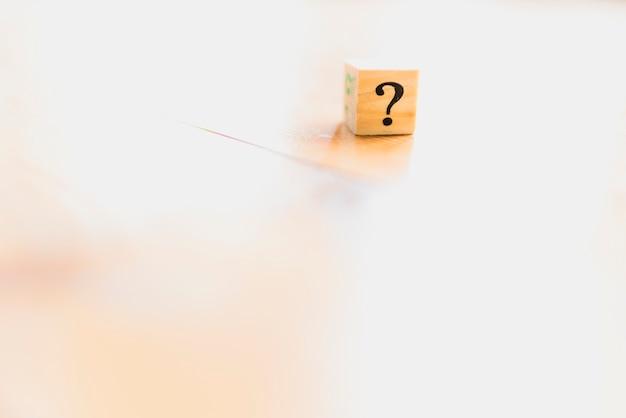 Dados de madeira com ponto de interrogação e dúvida.