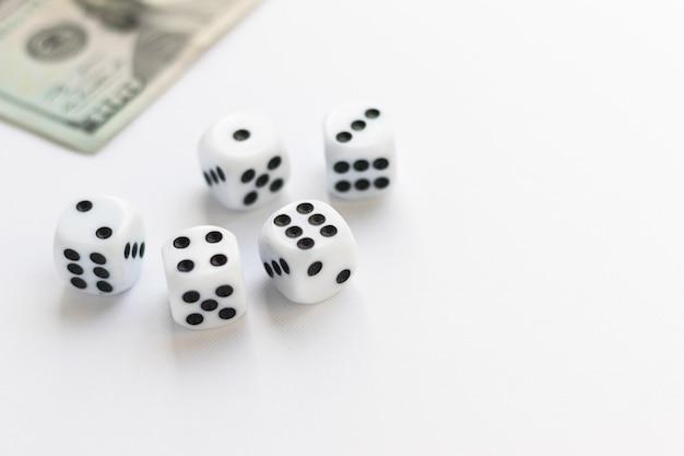 Dados e borrado 100 dólares americanos em branco. fortuna, vício em jogos. jogando cubo com números. itens para jogos de tabuleiro. camada plana, vista superior, espaço de cópia.
