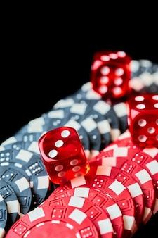 Dados e fichas vermelhos de cassino na mesa preta