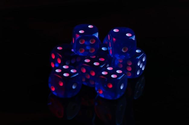 Dados em fundo preto com luz de néon azul vermelha