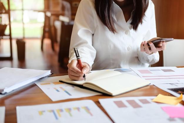 Dados fêmeas da análise da mulher de negócio no smartphone e escrita no papel do caderno.