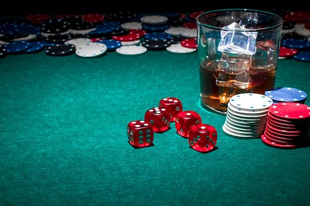Dados; fichas de poker e copo de uísque na mesa de jogo