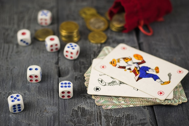 Dados, moedas e cartões coringa em uma mesa de jogo de madeira.
