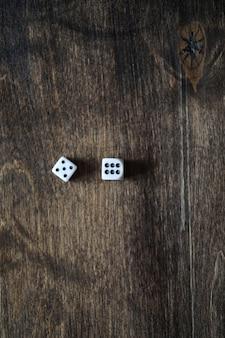 Dados pequenos brancos em uma mesa de textura de madeira marrom