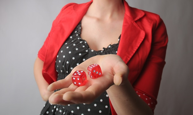 Dados vermelhos nas mãos de uma mulher com uma jaqueta vermelha